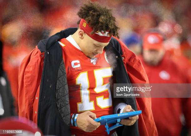 Kansas City Chiefs quarterback Patrick Mahomes looks at a tablet to review plays in the fourth quarter of an NFL Divisional round playoff game...