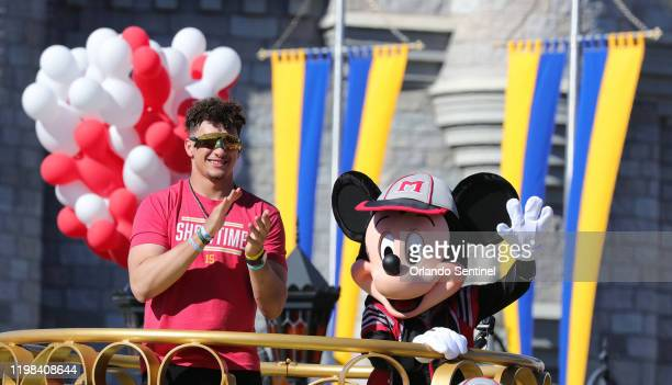 Kansas City Chiefs quarterback Patrick Mahomes responds to cheering fans with Mickey Mouse during a parade in the team's honor at the Magic Kingdom...