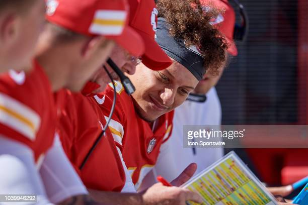 Kansas City Chiefs quarterback Patrick Mahomes reviews plays with Kansas City Chiefs head coach Andy Reid on the bench in action during an NFL game...