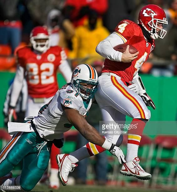 Kansas City Chiefs quarterback Tyler Thigpen scrambled for the last touchdown of the first half past the tackle of Miami Dolphins Akin Ayodele left...