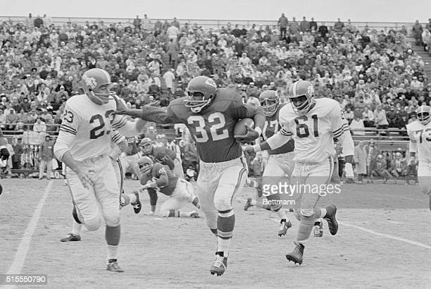 Kansas City Chiefs running back Curtis McClinton carries the ball on his way to a first down in a 1963 game against the Denver Broncos Pursuing...