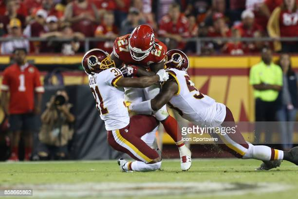 Kansas City Chiefs running back Kareem Hunt is tackled by Washington Redskins cornerback Fabian Moreau and inside linebacker Zach Brown in the fourth...
