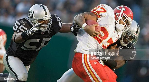 Kansas City Chiefs running back Larry Johnson picks up nine yards before being brought down by Oakland Raiders cornerback Hiram Eugene The Chiefs...