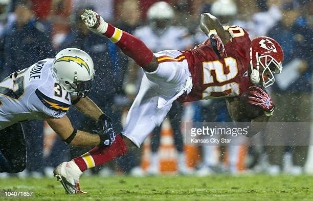 Kansas City Chiefs running back Thomas Jones is tripped up by San Diego Chargers safety Eric Weddle in the third quarter at Arrowhead Stadium in...