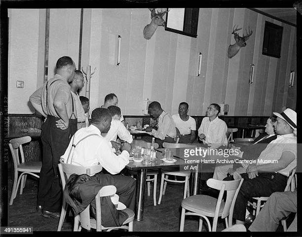 Kansas City Monarchs baseball pitcher Satchel Paige eating at Crawford Grill no 1, with onlookers including Bill Nunn Sr and Gus Greenlee seated on...
