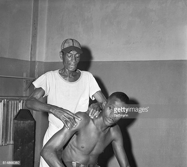 Kansas City Monarchs trainer Frank Floyd gives a shoulder rub to pitcher Satchel Paige, before a game against the New York Cuban Stars in Yankee...