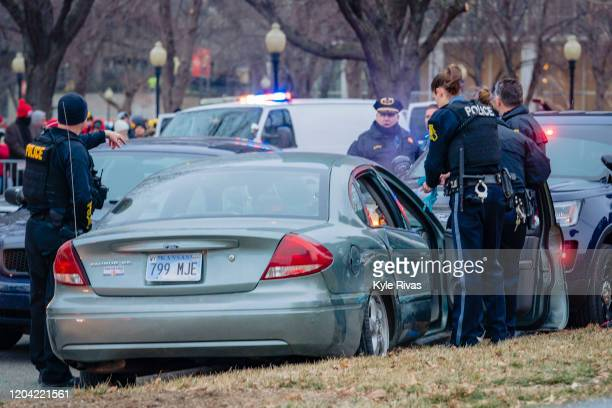 Kansas City Police inspect a car after a suspect led police on a chase down the main parade route on Grand Street three hours before the Kansas City...
