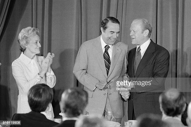 President Ford and his new vice presidential running mate Sen Robert Dole of Kansas holds hands as they make an appearance at a meeting of the...