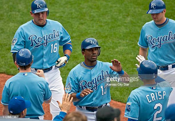 Kansas City Royals' Alberto Callaspo and Billy Butler are greeted at the dugout after both scored on an RBI triple by Kansas City Royals' John Buck...