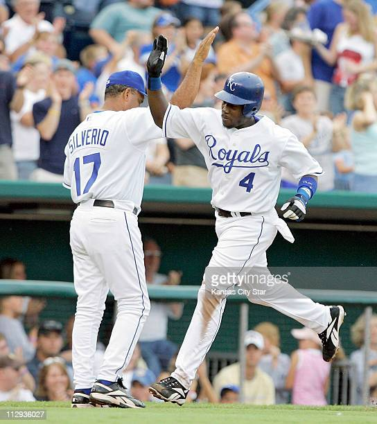 Kansas City Royals' Angel Berroa is congratulated by third base coach Luis Silverio after hitting a solo home run in the second inning on Saturday...