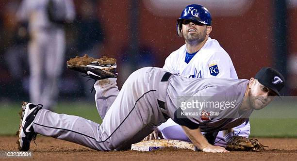 Kansas City Royals' David DeJesus peaks over Toronto Blue Jays second baseman Aaron Hill after Hill completed the double play in the fourth inning at...
