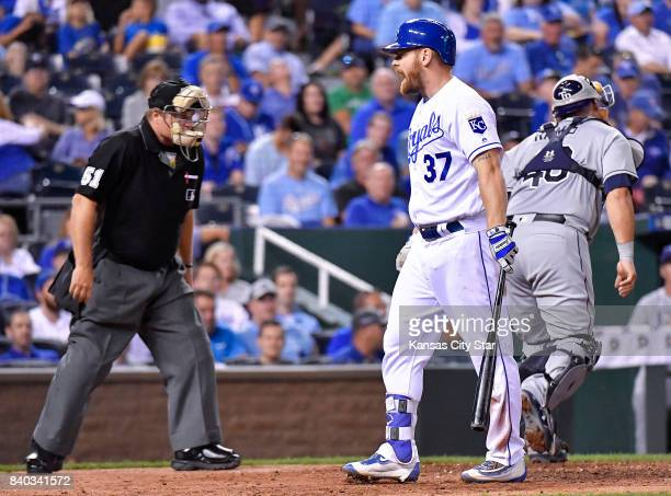 Kansas City Royals designated hitter Brandon Moss exchanges words with home plate umpire Marvin Hudson after being called out looking at strike three...