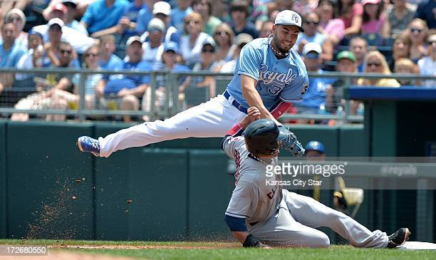 Kansas City Royals first baseman Eric Hosmer tried to get the tag down on Cleveland Indians' Michael Brantley after Carlos Santana lined out to...