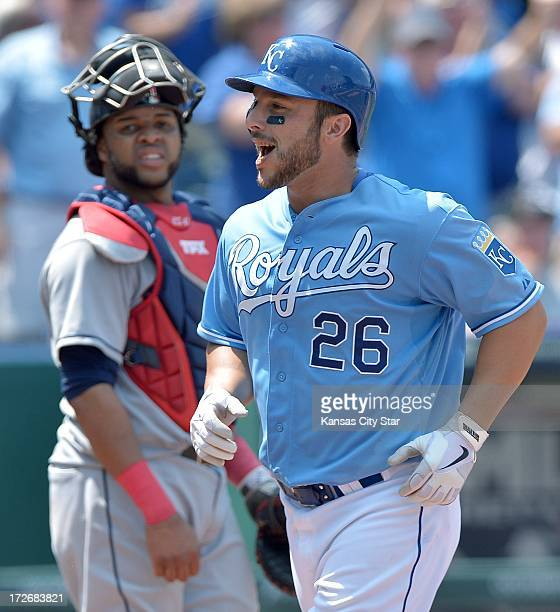 Kansas City Royals' George Kottaras smiles as he crosses the plate in front of Cleveland Indians catcher Carlos Santana following his solo home run...