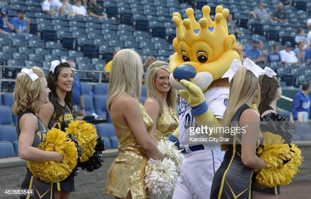Kansas City Royals mascot Sluggerrr waves to a group of University of Missouri cheerleaders before the Kansas City Royals play host to the Cleveland...