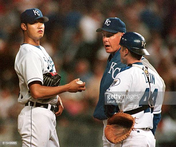 Kansas City Royals pitching coach Brent Strom confers with starting pitcher Mac Suzuki and catcher Gregg Zaun during the sixth inning against the...