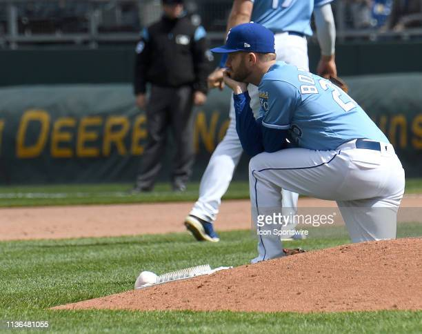 Kansas City Royals relief pitcher Brad Boxberger watches as Kansas City Royals center fielder Billy Hamilton is helped to his feat after hitting the...