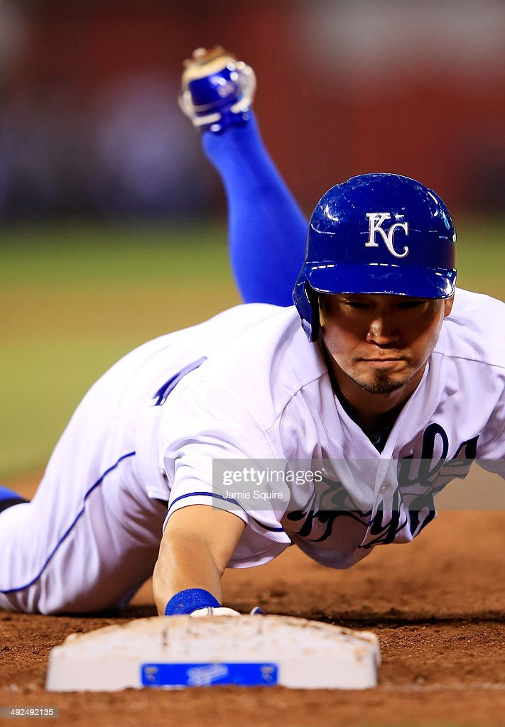 Kansas City Royals right fielder Norichika Aoki #23 dives back to first on a pickoff attempt during the 6th inning of the game against the Chicago White Sox at Kauffman Stadium on May 20, 2014 in Kansas City, Missouri.