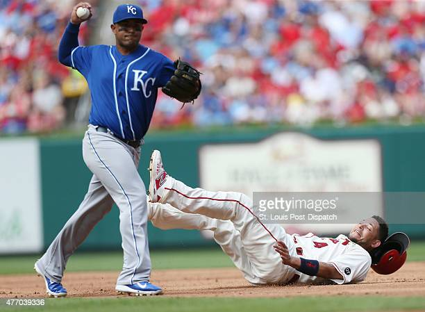 Kansas City Royals third baseman Christian Colon left throws errantly to first base after tagging out the St Louis Cardinals' Yadier Molina right at...