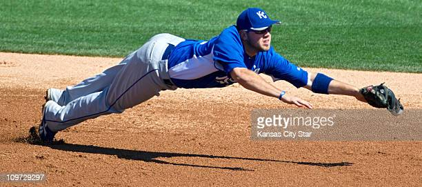 Kansas City Royals third baseman Mike Moustakas knocks down a grounder that shortstop Alcides Escobar picked up and threw to first for an out on the...