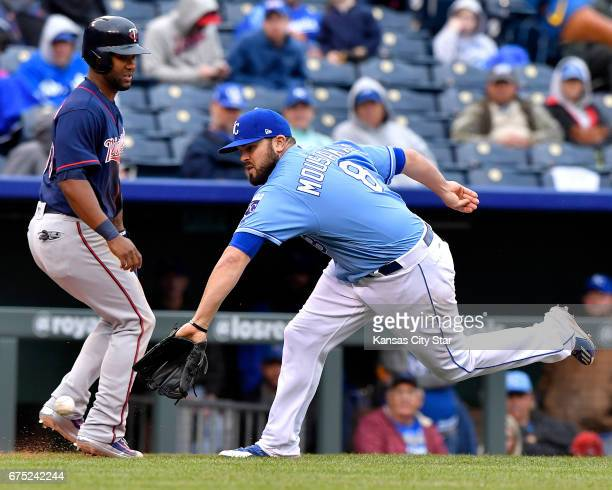 Kansas City Royals third baseman Mike Moustakas snags a grounder in front of Minnesota Twins' Danny Santana before throwing an error to first...