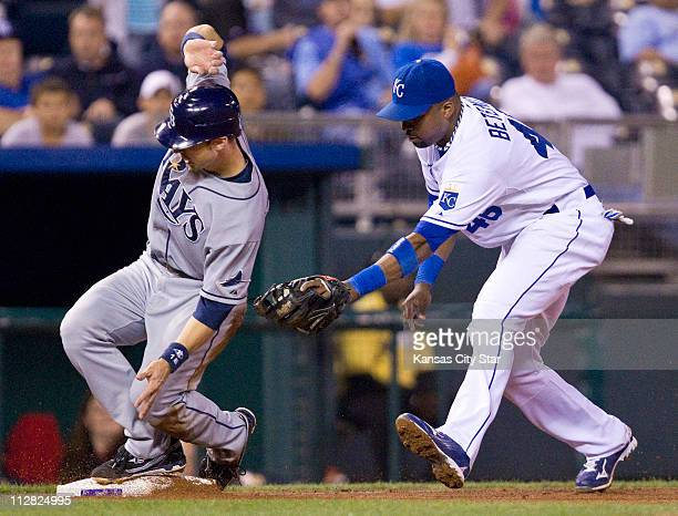 Kansas City Royals third baseman Wilson Betemit, right, chases after Tampa Bay Rays' Ben Zobrist as he tags up and takes third on a sacrifice fly by...