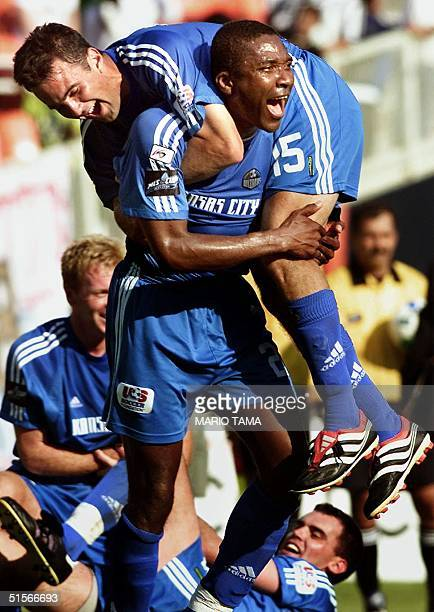 Kansas City Wizards' defenseman Uche Okafor carries Wizard midfielder Kerry Zavagnin off the field in celebration after defeating the Chicago Fire 10...