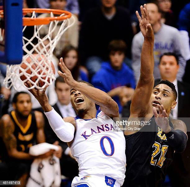 Kansas' Frank Mason muscles up a shot after driving by Towson defender Jerrelle Benimon during the first half at Allen Fieldhouse in Lawrence Ks...
