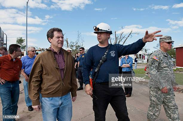 Kansas Gov Sam Brownback and John Troyer Captain of the Sedgwick County Fire Department tour the tornadodamaged Pinaire Mobile Home Park on April 15...