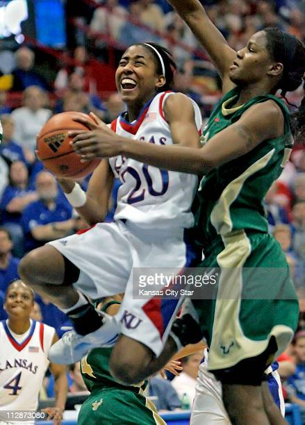 Kansas guard Sade Morris scores around South Florida center Brittany Denson during the women's NIT championship game at Allen Fieldhouse in Lawrence...