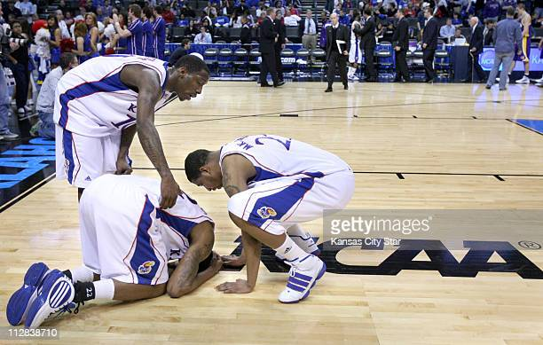 Kansas guard Tyshawn Taylor and forward Markieff Morris try to comfort teammate Marcus Morris after Kansas lost 6967 to Northern Iowa in the second...