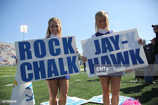 Kansas Jayhawk cheerleaders hold signs reading Rock Chalk Jayhawk during a game against the Oklahoma State Cowboys on October 11 2014 in Lawrence...
