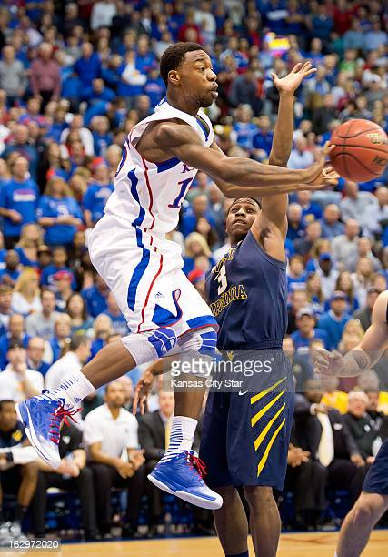 Kansas Jayhawks guard Elijah Johnson passes behind West Virginia Mountaineers guard Juwan Staten in the first half at Allen Fieldhouse in Lawrence...