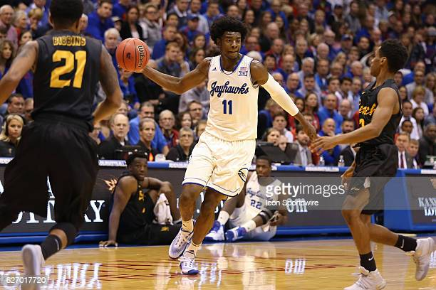 Kansas Jayhawks guard Josh Jackson looks to make a bounce pass between Long Beach State 49ers guards Justin Bibbins and Loren Jackson in an NCAA...
