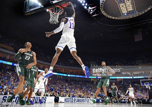 Kansas' Josh Jackson flies in for a dunk as Michigan State's Miles Bridges looks on during the first half on Sunday March 19 2017 in the second round...