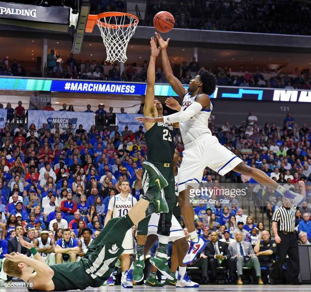 Kansas' Josh Jackson who scored a gamehigh 23 points bowls over Michigan State's Kyle Ahrens and Kenny Goins in a 9070 drubbing of the Spartans on...
