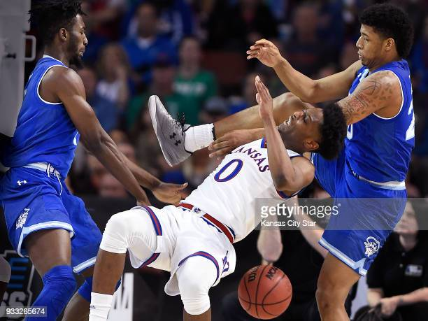 Kansas' Marcus Garrett middle is roughed up by Seton Hall's Myles Cale left and Desi Rodriguez during the second half in the second round of the NCAA...