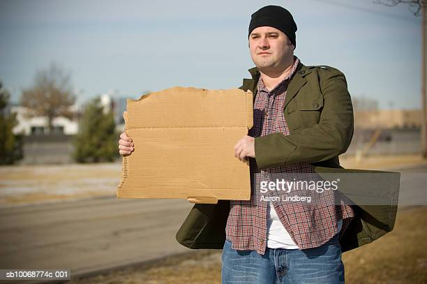 USA, Kansas, Olathe, young man holding sign on roadside