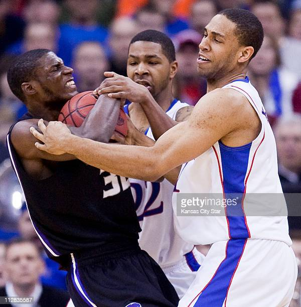 Kansas State forward Jamar Samuels gets caught in a trap by Kansas forward Marcus Morris and Kansas guard Xavier Henry during action in the...