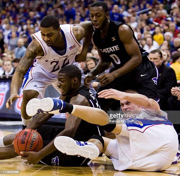 Kansas State forward Jamar Samuels wrestles the ball out of the hands of Kansas center Cole Aldrich as Kansas forward Marcus Morris and Kansas State...