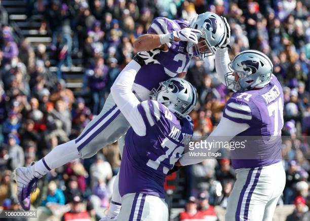 Kansas State running back Alex Barnes celebrates a touchdown with teammates offensive linemen Adam Holtorf and Dalton Risner against Kansas at Snyder...