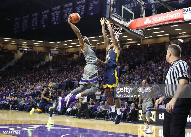 Kansas State Wildcats forward Xavier Sneed goes high attempting to dunk over West Virginia Mountaineers forward Sagaba Konate in the first half of a...