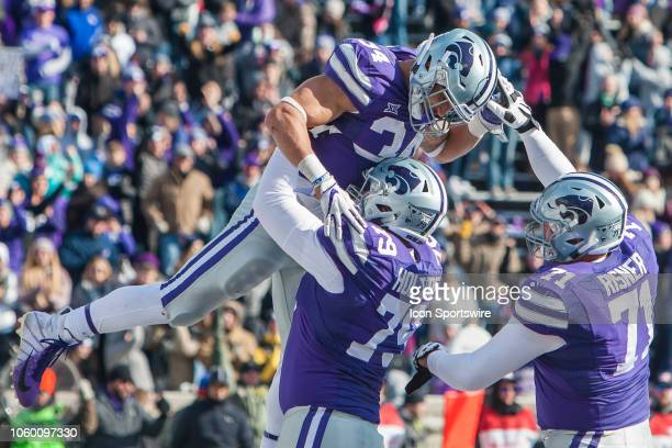 Kansas State Wildcats running back Alex Barnes celebrates with Kansas State Wildcats offensive lineman Dalton Risner is hoisting into the air by...