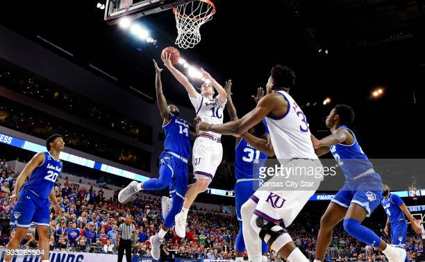 Kansas' Svi Mykhailiuk middle soars between Seton Hall defenders Ismael Sanogo and Angel Delgado for a bucket during the first half during the second...
