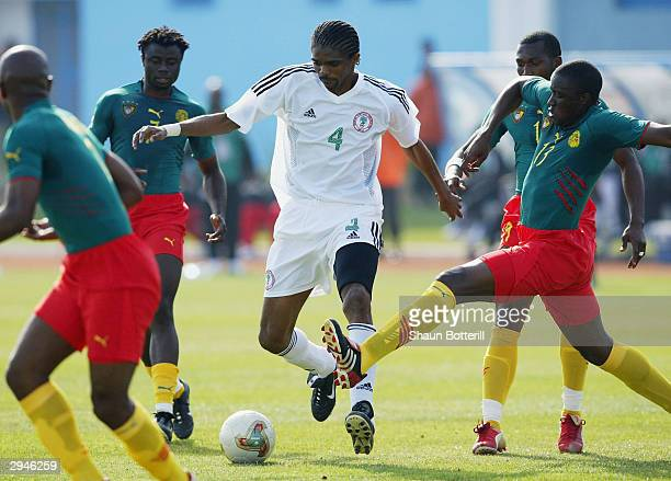 Kanu of Nigeria tries to break through the Cameroon defence during the African Nations Cup 2004 1/4 Final match between Cameroon and Nigeria at the...