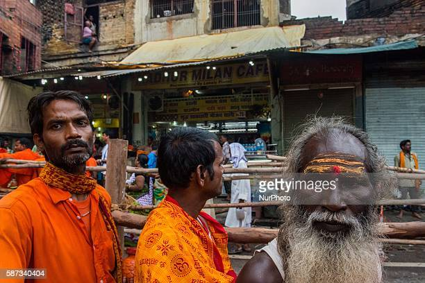 Kanwariya waits at queue at Kashi Vishwanath Temple after fill his pots with holy water from the river Ganga for the betterment of his family and the...