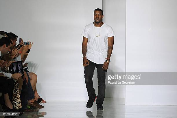 Kanye West acknowledges the applause of the audience after the Dw by Kanye West Ready to Wear Spring / Summer 2012 show during Paris Fashion Week at...
