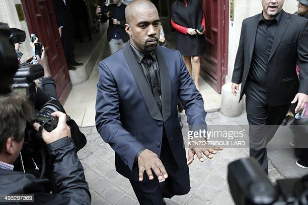 Kanye West gestures as he leaves his hotel on May 23 2014 in Paris Hip hop star Kanye West and reality TV celebrity Kim Kardashian are expected to...