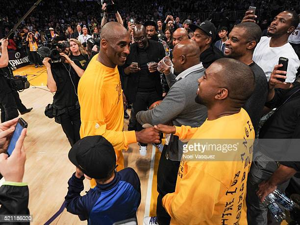 Kanye West greets Kobe Bryant at a basketball game between the Utah Jazz and the Los Angeles Lakers at Staples Center on April 13 2016 in Los Angeles...