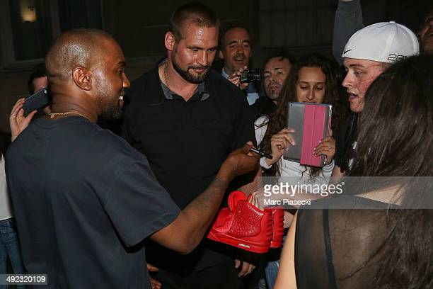 Kanye West signs sneakers as he leaves the 'Ferdi' restaurant on May 19 2014 in Paris France